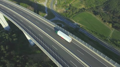 AERIAL: Container truck driving along the empty freeway