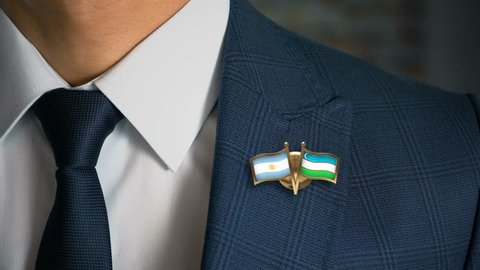 Businessman Walking Towards Camera With Friend Country Flags Pin Argentina - Uzbekistan