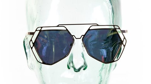 a clear glass mannequin head with amazing changing collection of sunglasses and shades