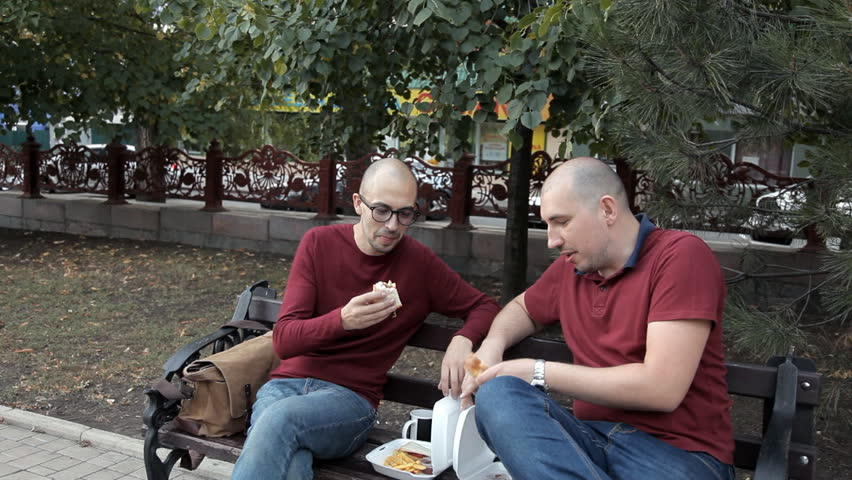 Two bald guys are sitting in the park and eating sandwiches and French fries. Delicious food, fast food | Shutterstock HD Video #1017263440