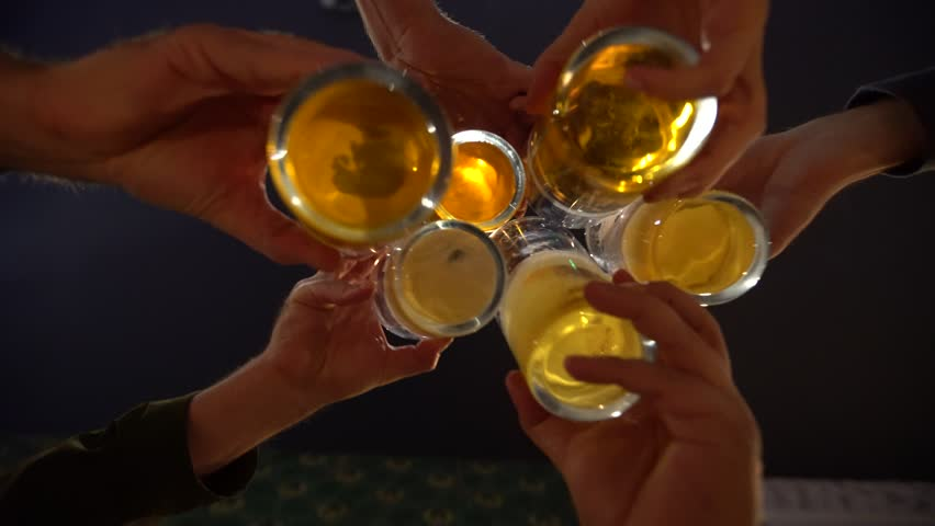 Men toast with the mugs of beer, bar at night. Alcohol and socializing. Pints of alcoholic lager drinks. Dark scene. | Shutterstock HD Video #1017296590