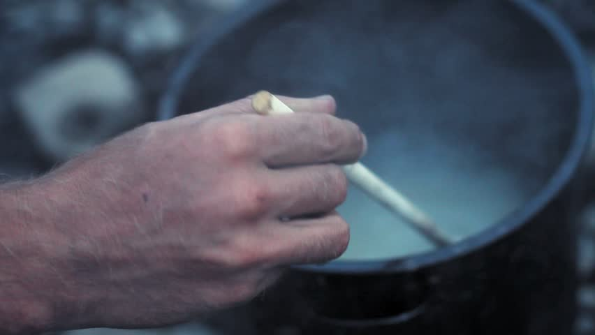 Yukon river, Yukon Territory, Alaska. Night camp of a canoe expedition to Alaska. Cooking rice in a pot while hand with wooden spoon stirs the boliling water.