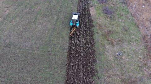 Tractor plowing the garden. Plowing the soil in the garden. Plowing field