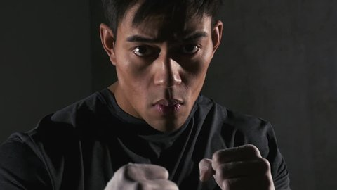 Asian boxer throwing punches at camera. Close up.