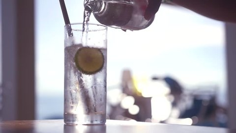Pour refreshing sparkling water from a bottle into a glass with ice and a slice of lime. HD, 1920x1080, slow motion