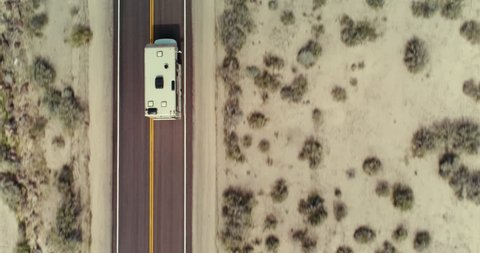 AERIAL - Topdown view of an RV in the desert while the camera tilts up and shows the RV driving towards a landscape