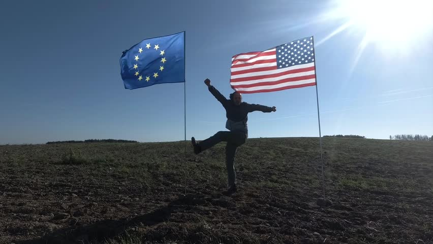 Concept on the international relations, international partnership of US and European Union. Silhouette of man on the background of the American and European flag. #1017393430