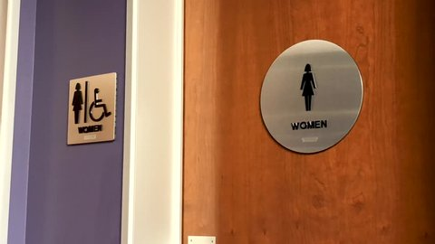 Women's bathroom sign on wooden door in corporate office environment.
