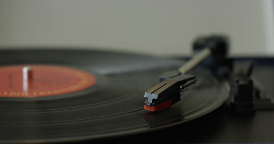 Womans hand takes needle off of playing vinyl record - close up