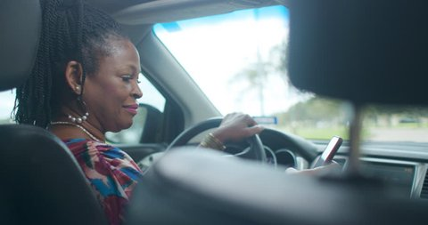 An Uber of Lyft type driver checks the ride sharing app on her smart phone to verify the assignment then engages passenger in friendly conversation.
