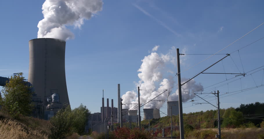 RWE power plant working on lignite brown coal producing electricity and huge clouds of steam in Neurath, global warming Germany, sunny day, 4K