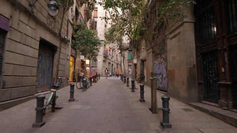 BARCELONA, SPAIN - AUGUST 13, 2018: Walking up along nice Carrer d'Ataulf, old street at Gothic Quarter of Barcelona, first person view. Small trees and bollards at sides, closed doors of shops