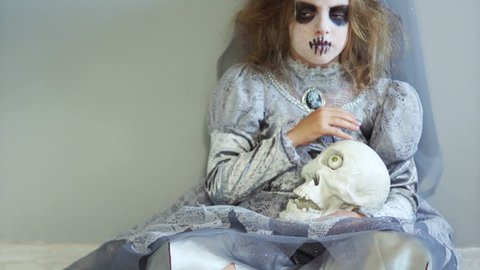 A child in make-up and costume of the bride of Dracula celebrates Halloween. Girl holding a skull. Sighing and sad, looking at the camera