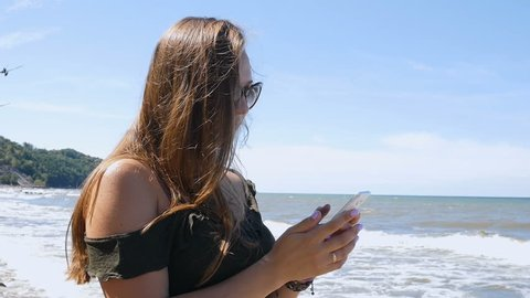 Medium shot of a beautiful young woman running hand through hair blowing in the wind to the beach