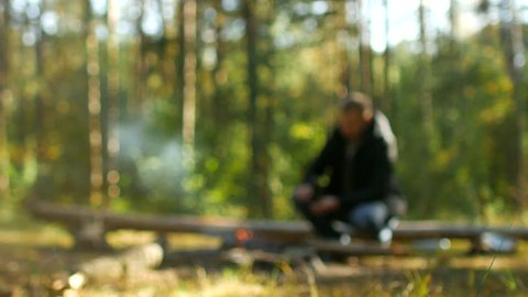 A man kindles a fire in the woods in nature, outdoor recreation, blurry, background, camping