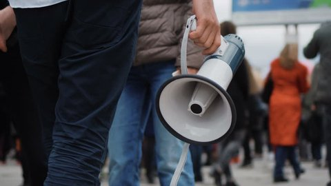 1 Man holds a megaphone in his hands, walking down street through many people on strike. Close up of one guy with loudspeaker in crowd at a demonstration 4k. Young adult boy on revolution.