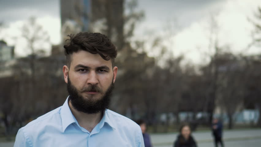 A serious man with a beard and mustache looks into the camera close-up. The look of the guy in the blue shirt is a closeup. Portrait of an office worker in the park. Young adult boy outside in city. #1017522520