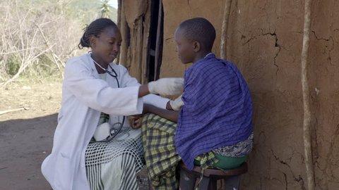 Nurse examining female patient. Maasai village. Kenya.