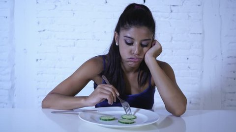 Portrait o f young attractive woman feeling sad and bored with diet not wanting to eat vegetables or healthy food in Dieting Eating Disorders and weight loss concept.