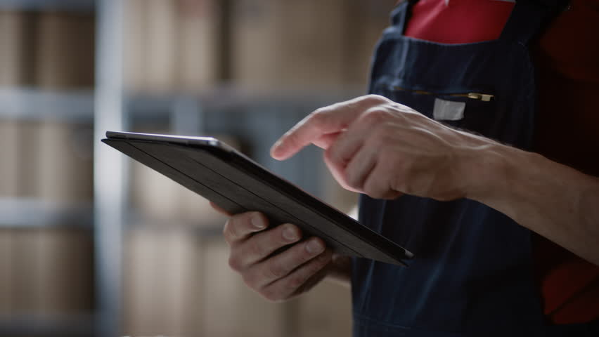 Close-up on a Man's Hands Using Digital Tablet Computer while Standing in the Warehouse. | Shutterstock HD Video #1017604630