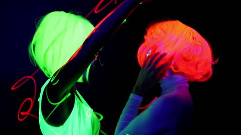 Beautiful sexy women with laser, UV face paint, wig, glowing glasses, glowing clothing dancing together fast in front of camera, Half body shot. Caucasian and asian woman. Party concept.