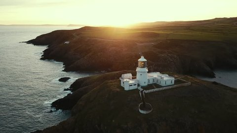 Pembrokeshire, Wales UK- Aerial view of Strumble Head lighthouse at sunrise on the pembrokeshire coastine