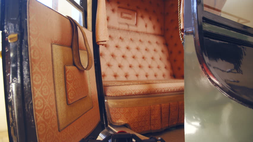 Dolly slide zoom-in to a vintage carriage inside 4K. Camera slide towards the inside the vintage carriage in focus with a stylish seat.