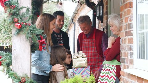 Family Being Greeted By Grandparents As They Arrive For Visit On Christmas Day With Gifts