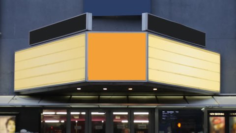 A daytime view of a theater's blank marquee in a large city as pedestrians and traffic pass by.