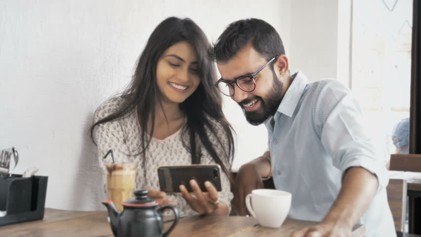 A young couple are laughing while watching a funny video on a smartphone or cellphone sitting in modern coffee shop. Two happy and joyous friends watching a movie on a mobile phone in a cafe interior