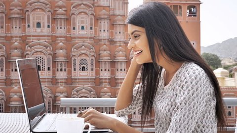 A happy and cheerful young woman in traditional kurta is using laptop to talk on video call. A  movement shot of a smiling and attractive girl chatting on video call with a friend in exterior setup