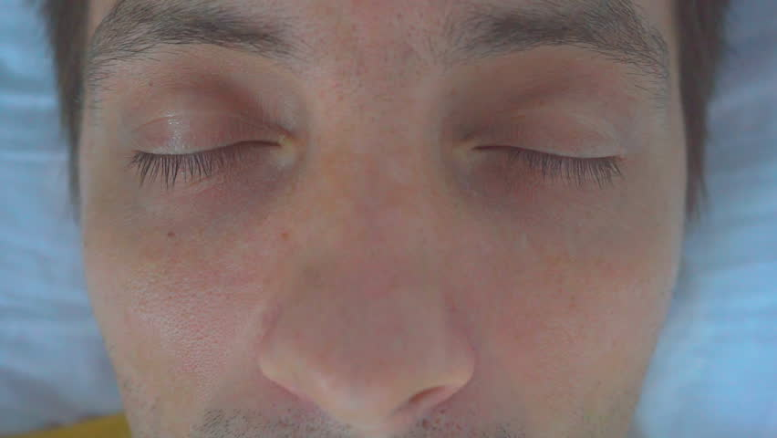 Man abruptly opens his eyes in a hospital bed.   Shutterstock HD Video #1017816730