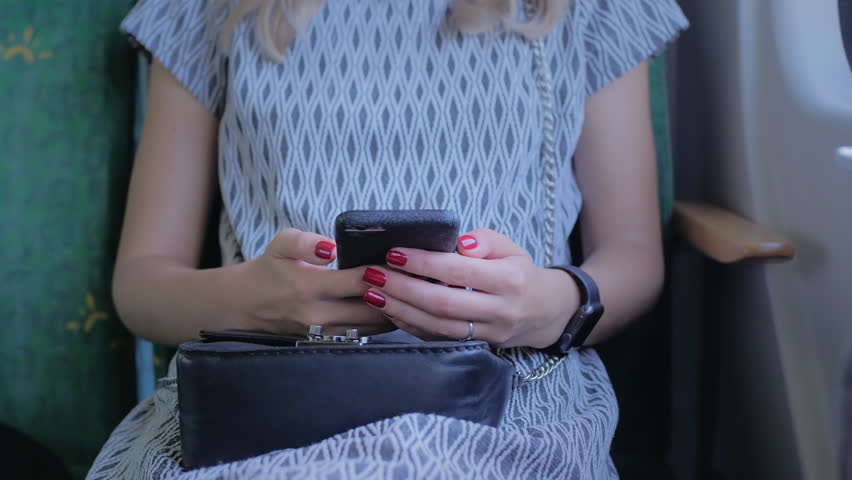 Young unrecognizable girl with beautiful red nails, sitting in the seat of an airplane, train or bus. Uses a mobile smartphone. Slow Motion Close-up. | Shutterstock HD Video #1017830200