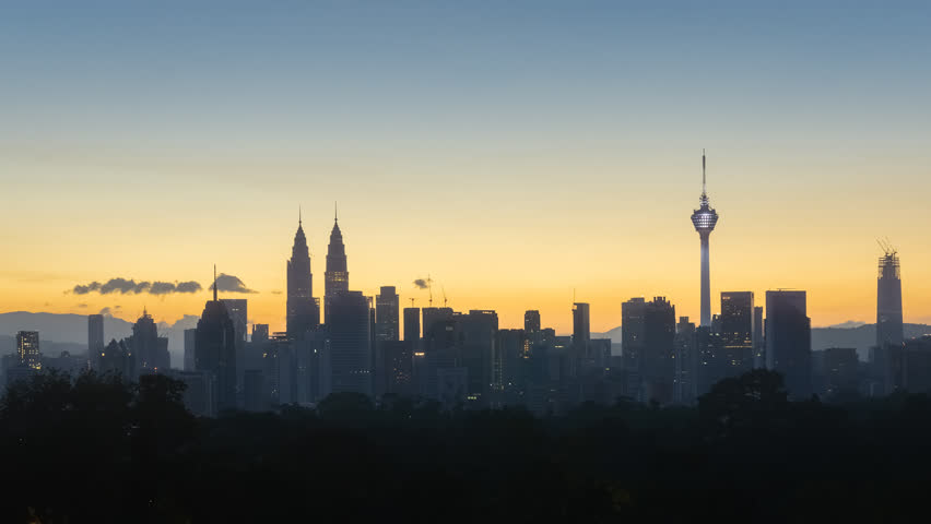 Time lapse: Silhouette of Kuala Lumpur city view during dawn overlooking the city skyline from afar with lushes green in the foreground. Federal Territory, Malaysia. Full HD.
