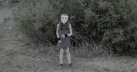 young girl wearing a white halloween mask stands spookily and then runs in scary manner towards the camera