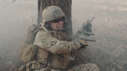 The soldier in a panic hides behind a tree during fight in forest