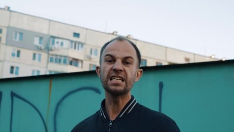 Angry man shouting at someone in the ghetto