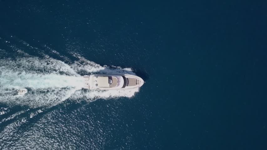 Medium sized Yacht roaring across The Mediterranean Sea - Top down aerial footage following the Yacht. | Shutterstock HD Video #1017898150