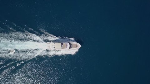 Medium sized Yacht roaring across The Mediterranean Sea - Top down aerial footage following the Yacht.