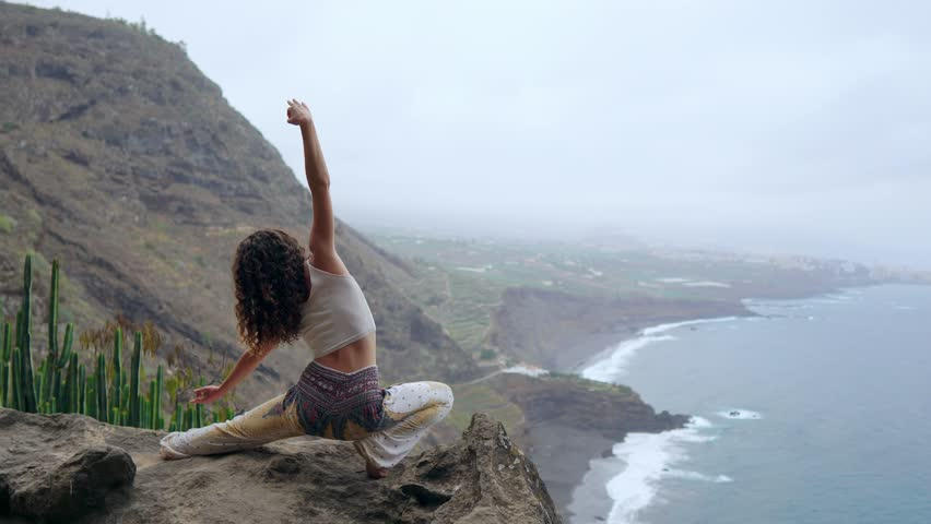 A woman sitting on the edge of a cliff in a pose war overlooking the ocean raise her hands up and inhale the sea air while doing yoga | Shutterstock HD Video #1017905560