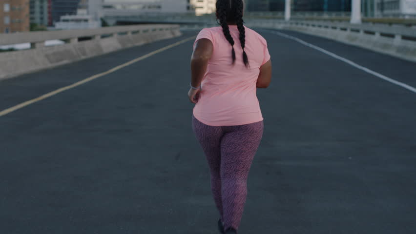 Overweight woman athlete runner exercising running weight loss workout jogging in urban city background at sunrise rear view   Shutterstock HD Video #1017906730