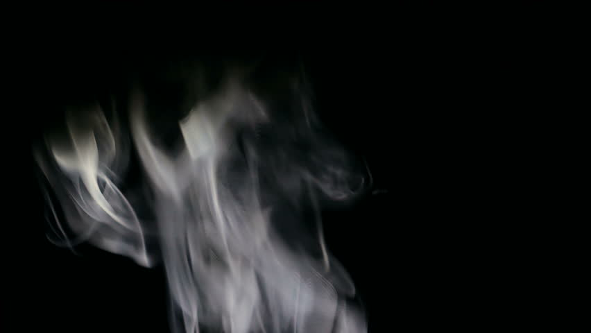 White smoke over a black background. Smoke slowly floating through space against black background.