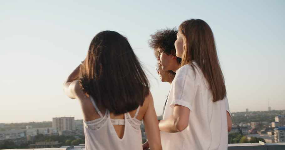 Group of five multiethnic friends hanging out on summer rooftop party, talking, cheering, having fun 4k
