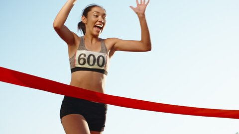 Female athlete on track. Young asian runner runing on track of stadium, happily crossing the red finish line, getting ready for competition 4k