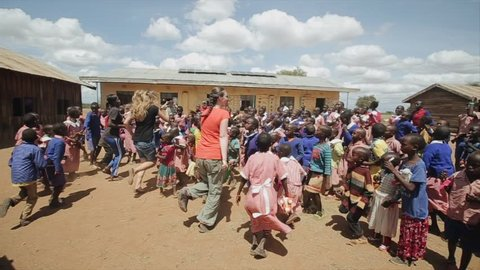KENYA, KISUMU - MAY 20, 2017: Caucasian women dancing with African children outside the school building.