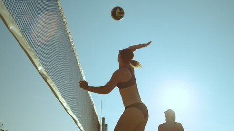 SLOW MOTION, CLOSE UP, LENS FLARE, LOW ANGLE: Athletic young Caucasian women in bikinis playing beach volleyball in the bright summer sun. Fit girls having fun playing volleyball in their bikinis.