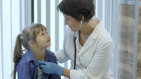 Kind female pediatrician using stethoscope to listen to breath sounds of cute little patient during medical examination in hospital, medium shot