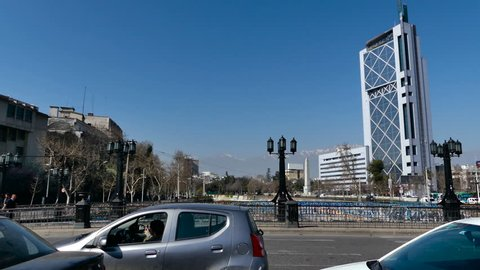 SANTIAGO, CHILE - Sep 11 2018. Cars waiting, then moving on the Pio Nono bridge. View of the Telephone Tower, Andes mountains, Plaza Italia Obelisk and Mapocho River near the Baquedano Plaza.