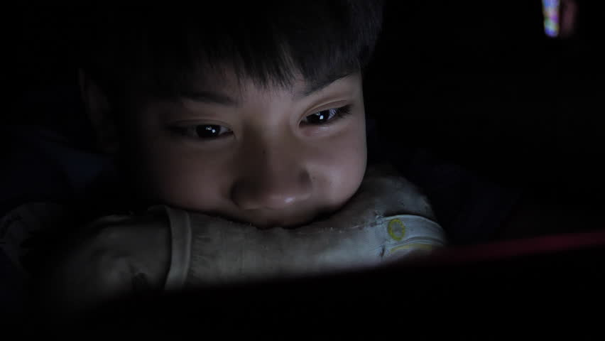 Young asian boy playing with a cellphone or smartphone on a bed. night   Shutterstock HD Video #1017990550