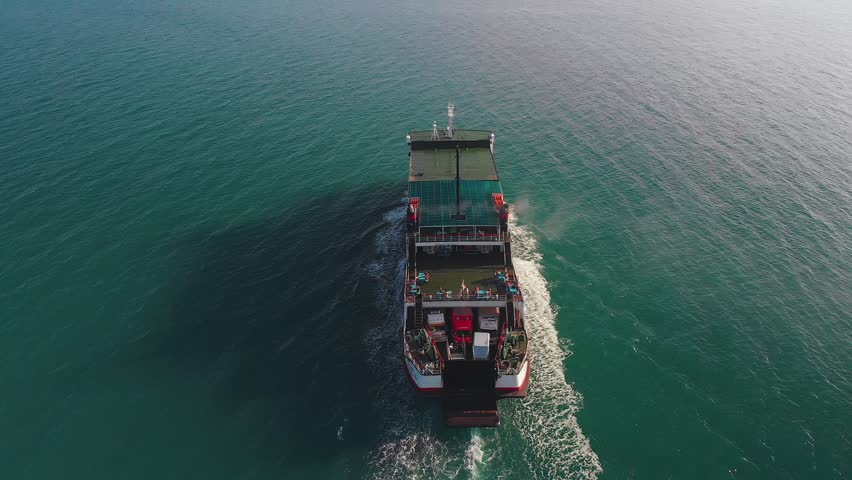 Above the ferry going on the sea. The ferry boat carries passengers and transport along the green sea | Shutterstock HD Video #1017998440